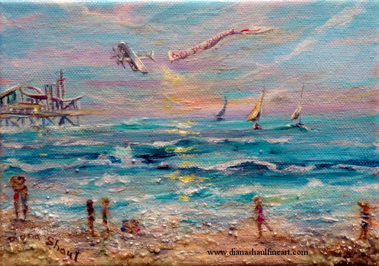 Beach scene with people along shore, a pier in the distance, sailboats on the water and a plane pulling a banner in the sky.