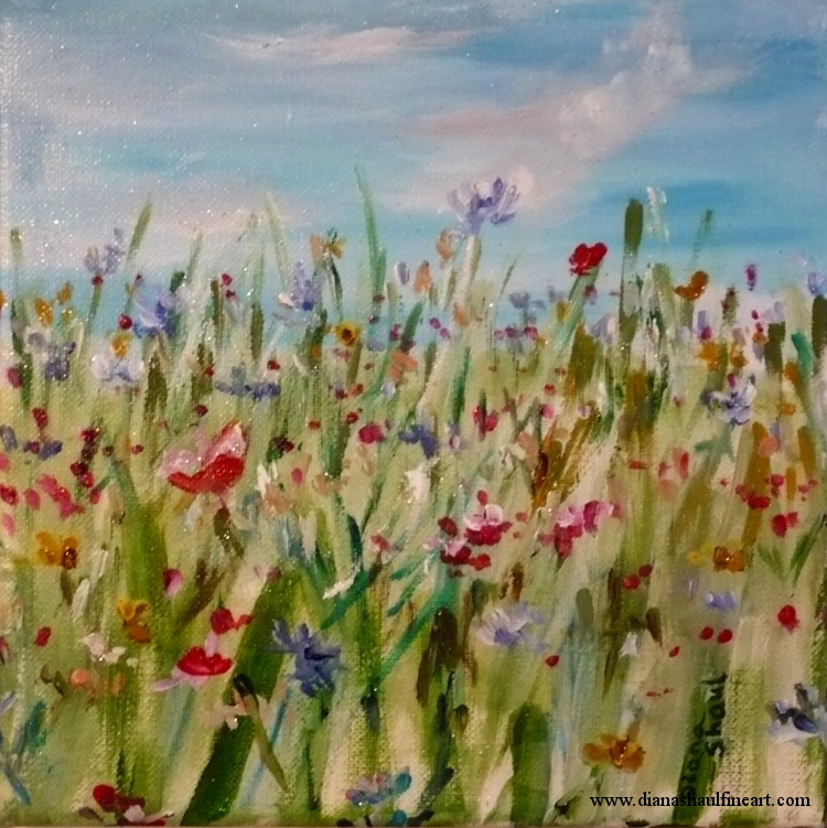 A meadow of flowers in shades of yellow, red and blue, a clear sky above.